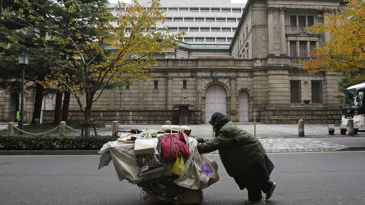 Un homme pousse un chariot devant la Banque du Japon à Tokyo, le 26 novembre 2012. (YURIKO NAKAO / REUTERS)