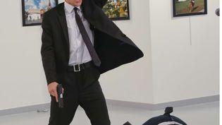 Un homme identifié comme étantMevlüt Mert Altintas se tient à côté du corps de de l'ambassadeur russe en Turquie, Andrei Karlov, après lui avoir tiré dessus le 19 décembre 2016à Ankara. (BURHAN OZBILICI/AP/SIPA / AP)