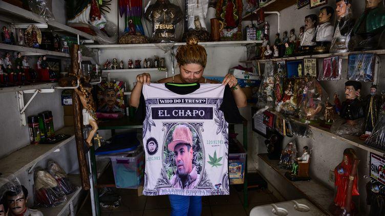"""Un vendeur montre un t-shirt à représentant Joaquin """"El Chapo"""" Guzman dans un magasin situé à Culiacan, dans l'État de Sinaloa, au nord-ouest du Mexique, le 15 juillet 2019. (PEDRO PARDO / AFP)"""