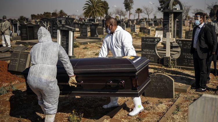 Des salariés des pompes funèbres déplacent un cercueil contenant une victime du Covid-19 au cimetière d'Avalon à Soweto (Afrique du Sud), le 24 juillet 2020. (MICHELE SPATARI / AFP)