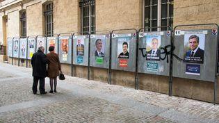 Deux passants devant les affiches de campagne des candidats à l'élection présidentielle, le 10 avril 2017, à Paris. (DANIEL FOURAY / MAXPPP)