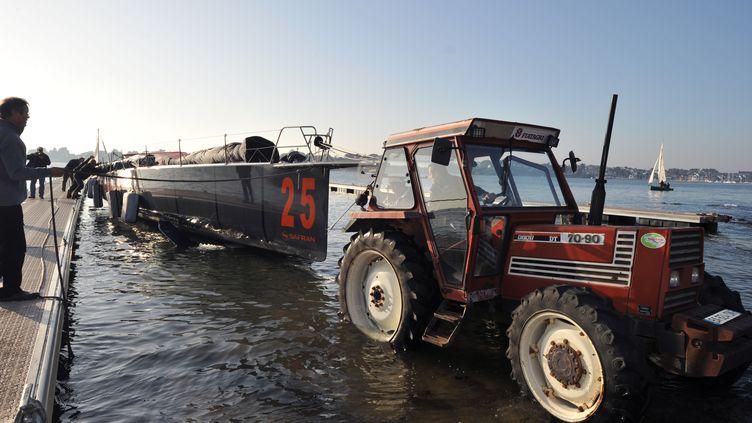 """Le bateau """"Safran"""" de Marc Guillemot est remorqué hors de l'eau par un tracteur, après son abandon lors du Vendée Globe, le 14 novembre 2012, à Saint-Philibert. (FRANK PERRY / AFP)"""