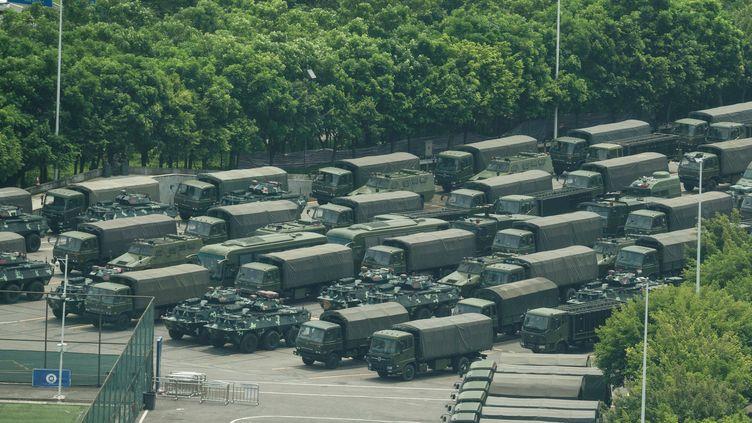 Des chars et personnels armés dans la baie de Shenzhen, à la frontière hongkongaise et à proximité du stade où des entraînements militaires de grande empleur ont lieu, le 15 août 2019. La crainte d'une intervention musclée est grandissante. (STR / AFP)