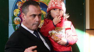 Robert Lawrie porte la petite afghane Bahar Ahmadi, le 14 Janvier 2016 dansles couloirs du tribunal à Boulogne-sur-Mer avant le début de son procès. (DENIS CHARLET / AFP)
