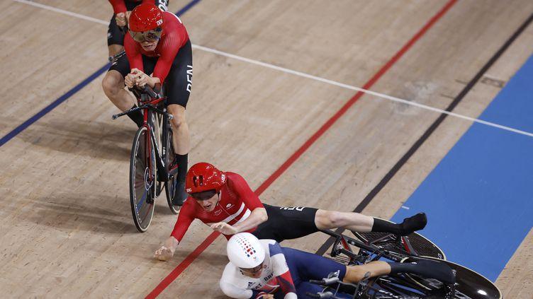 Frederik Madsen (en rouge) et Charlie Tanfield (en blanc) se sont percutés pendant l'épreuve de poursuite par équipes, à Tokyo le 3 août 2021. (ODD ANDERSEN / AFP)