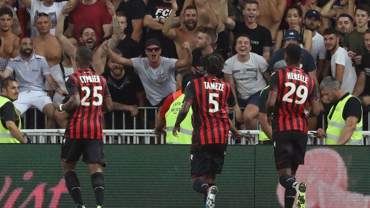 Les joueurs de l'OGC Nice Cyprien, Tameze et Herelle vont parler aux supporters pendant l'interruption du match contre l'OM à cause de chants et banderoles homophobes, le 28 août 2019, à l'Allianz Riviera, à Nice. (VALERY HACHE / AFP)