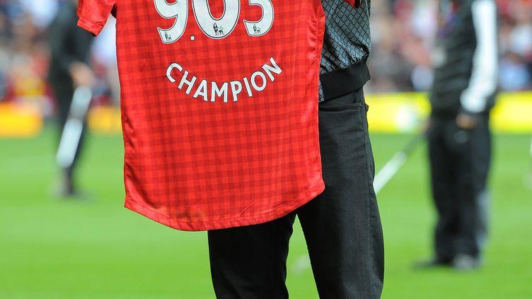 Usain Bolt prend la pose avec son maillot de Manchester United. (ANDREW YATES / AFP)