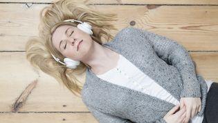Une jeune femme écoute de la musique au casque. (ULLSTEIN BILD DTL. / GETTY IMAGES)