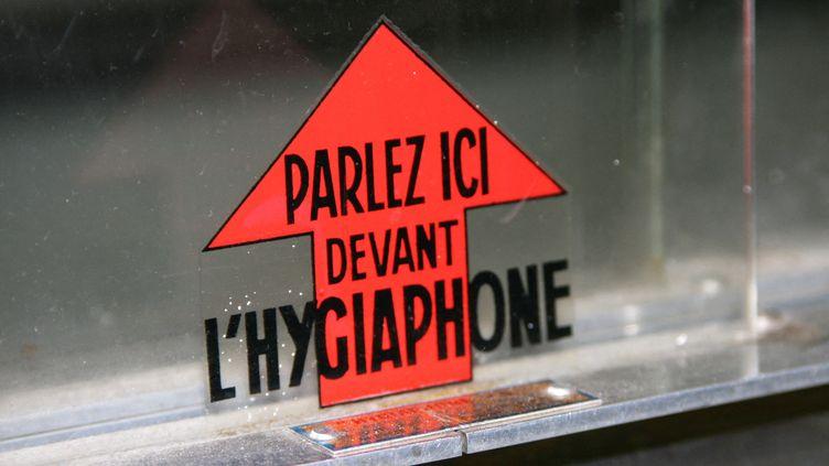 """Auto-collant à un guichet vitré indiquant """"Parlez ici devant l'hygiaphone"""". (CATHERINE GRAIN / RADIOFRANCE)"""