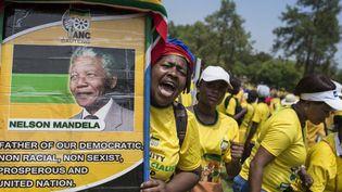 Une femme membre du Congrès national africain brandit le portrait de Nelson Mandela lors d'une manifestation contre le racisme, le 19 février 2016 à Pretoria. (Photo AFP/Ihsaan Haffejee)