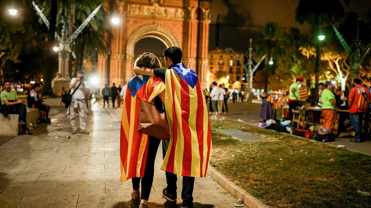 Deux personnesportent le drapeau indépendantiste catalan dans les rues de Barcelone, le 10 octobre 2017. (GONZALO ARROYO MORENO / ANADOLU AGENCY / AFP)
