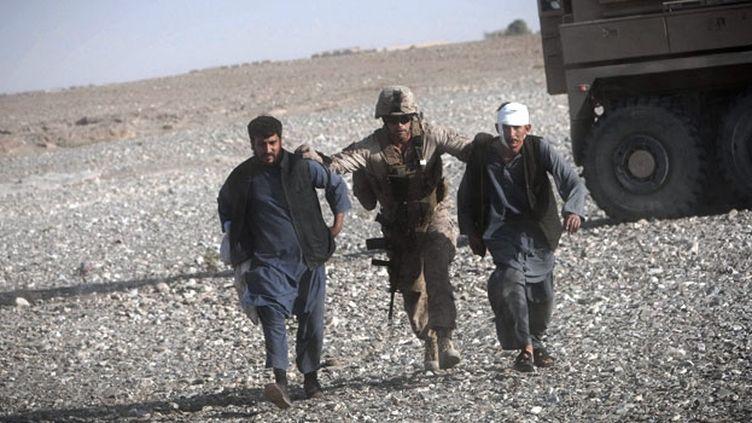 Un Marine américain aide des Afghans, blessés par des tirs d'insurgés, à rejoindre l'hélicoptère de l'unité médicale aérienne. (AFP PHOTO / BEHROUZ MEHRI)