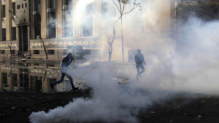 Des manifestants égyptiens fuient les gaz lacrymogènes lancés par la police le 4 février 2012 au Caire (Egypte). (MAHMUD HAMS / AFP)
