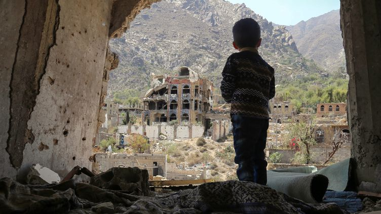 Un jeune enfant contemple la ville de Taez, dans le sud du Yémen, détruite par des frappes aériennes, le 18 mars 2018. La guerre civile qui secoue le pays depuis l'été 2014 a fait plus de 10 000 morts. Début 2018, un Yéménite sur quatre était au bord de la famine en raison du conflit. (AHMAD AL-BASHA / AFP)