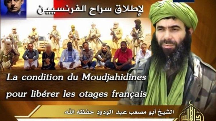 Abou Moussab Abdul Wadud, le chef d'Al-Qaïda au Maghreb islamique (AQMI), en arrière plan les otages français enlevés (AFP PHOTO/SITE/HANDOUT)