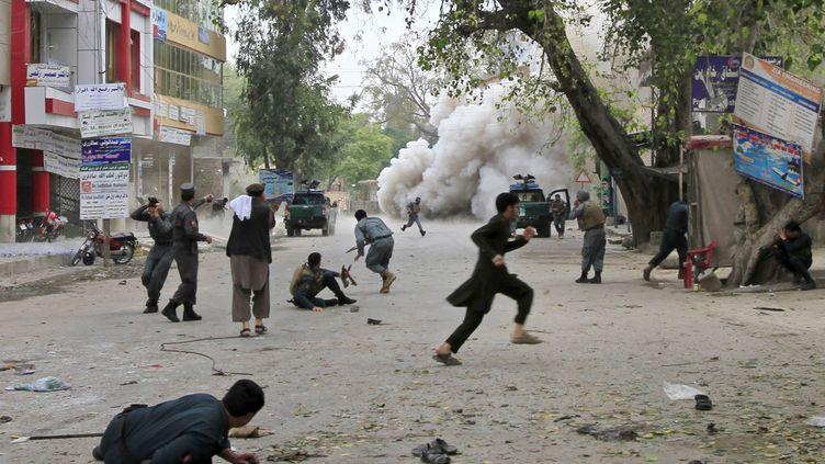 Des passants courent pour se cacher après une explosion à Jalalabad (Afghanistan), le 18 avril 2015. (PARWIZ / REUTERS)