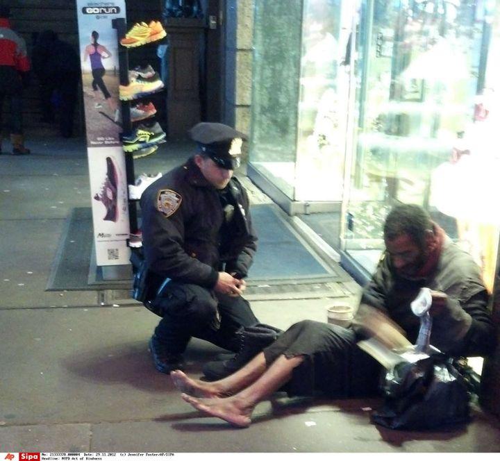 Une passante a photographié, le 14 novembre 2012 à New York, un policier apportant des bottes à un SDF. Posté sur la page Facebook de la police new-yorkaise, le cliché a fait le tour des Etats-Unis. (JENNIFER FOSTER / SIPA / AP)