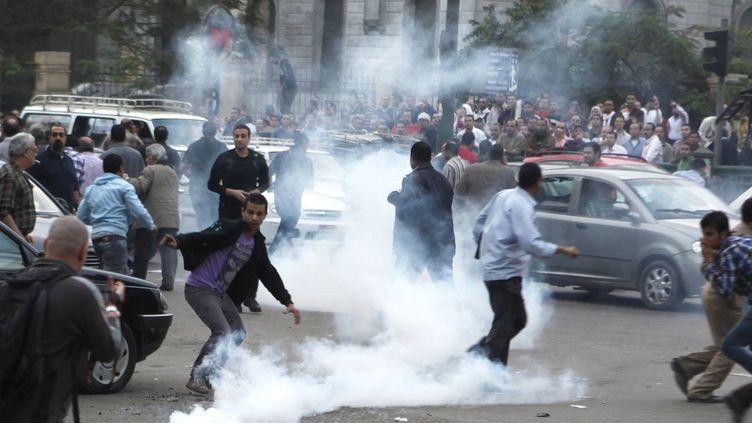 Des opposants au président égyptien, MohamedMorsi, affrontent la police devant le Conseil suprême de la justiceau Caire (Egypte), le 24 novembre 2012. (ASMAA WAGUIH / REUTERS)