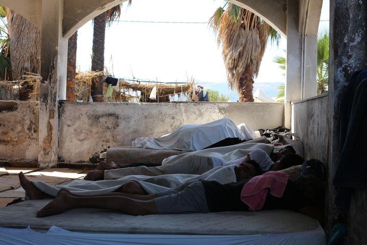 Des migrants pakistanais dorment sous l'ancienne véranda de l'hôtel Captain Elias, le 19 août 2015 à Kos (Grèce). (BENOIT ZAGDOUN / FRANCETV INFO)