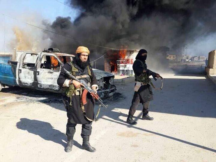 Une personne présentée comme un leader de l'Etat islamique en Irak et au Levant (G) se tient devant des voitures en feu, le 8 janvier 2014, dans un lieu indéterminé en Irak. (HANEIN.INFO / AFP)