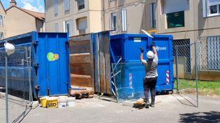 Un homme jette des déchets dans une poubelle, lors d'un chantier de réhabilitation de logements sociaux, à Valence (Drôme), le 18 juin 2020. (NICOLAS GUYONNET / HANS LUCAS / AFP)