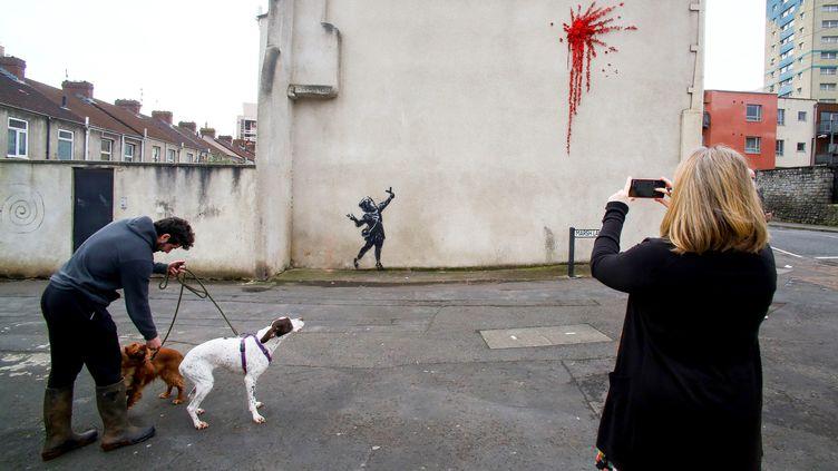 Des passants devant une œuvre de Banksy, à Bristol, le 14 février 2020. (GEOFF CADDICK / AFP)