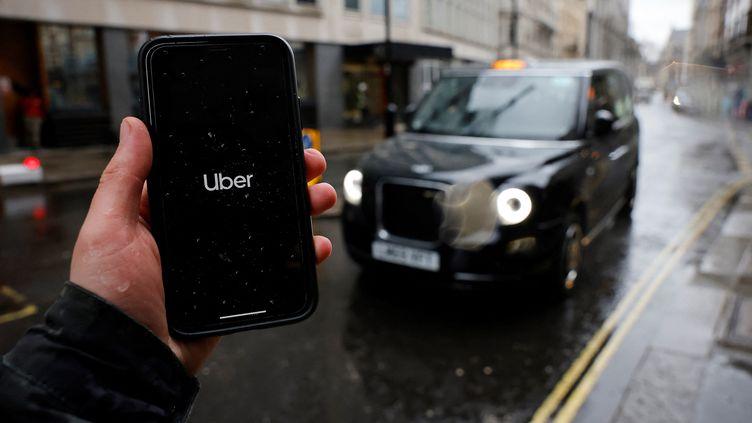 Un homme tient un smartphone montrant l'applicationUber à Londres, le 17 mars 2021. (TOLGA AKMEN / AFP)