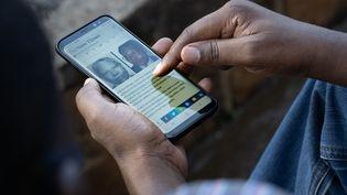 """Un hommesur son smartphone à Kigali, la capitale rwandaise, le 18 mai 2020. On y aperçoit un article du """"New Times"""" sur l'arrestation de Félicien Kabuga, l'un des principaux génocidairesqui échappaient encore à la justice. (SIMON WOHLFAHRT / AFP)"""
