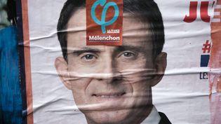 Une affiche de campagne de Manuel Valls recouverte par un autocollant de Jean-Luc Mélenchon, le 10 janvier 2017. (MAXPPP)