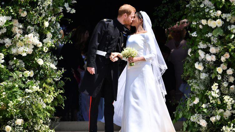 Le prince Harry et la duchesse Meghan s'embrassent à la sortie de la chapelle Saint George, à Windsor (Royaume-Uni), le 19 mai 2018. (BEN STANSALL / AFP)