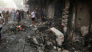 Des passants inspectent les débris après la déflagration, à Bagdad (Irak), le 3 juillet 2016. (SABAH ARAR / AFP)