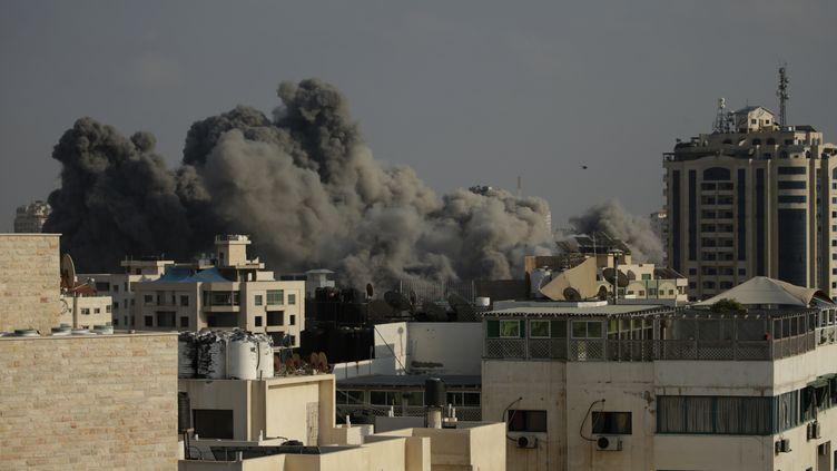 De la fumée s'échappe des immeubles à Gaza City après des frappes israéliennes, le 14 juillet 2018. (MAHMUD HAMS / AFP)