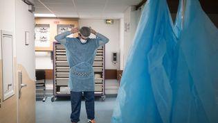 Un soignant enfile un équipement de protection dans les services d'urgence de l'hôpital Lariboisière à Paris, le 27 avril 2020 (photo d'illustration). (JOEL SAGET / AFP)