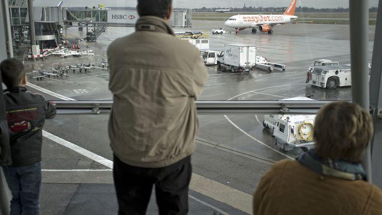 Passagers à l'aéroport de Lyon Saint-Exupéry devant le tarmac (JEAN-PHILIPPE KSIAZEK / AFP)