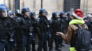 """Des membres des forces de l'ordre font face à une manifestante lors d'un rassemblement de """"gilets jaunes"""" à Paris, le 11 décembre 2018. (STEPHANE DE SAKUTIN / AFP)"""
