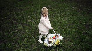 Une petite fille porte un panier rempli d'oeufs dans un parc à Donetsk (Ukraine), le 20 avril 2014. ( MARKO DJURICA / REUTERS)