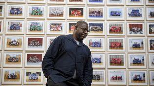 Steve McQueen devant une partie des photos de classes d'écoliers exposées à la Tate Britain, à Londres, le 11 novembre 2019 (TOLGA AKMEN / AFP)