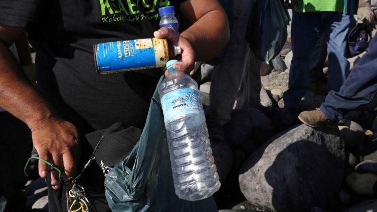 Parmi les objets trouvés sur la plage de Sainte-Marie de la Réunion, où se poursuit la recherche de débris de l'avion MH370, des bouteilles d'eau minérale avec des idéogrammes. (RICHARD BOUHET / AFP)