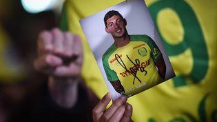 Un supporter brandit une photo dédicacée d'Emiliano Sala à Nantes (Loire-Atlantique), le 22 janvier 2019. (LOIC VENANCE / AFP)