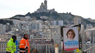 Deux personnes passent près d'une affiche de la candidate Les Républicains pour la mairie à Marseille, Martine Vassal, le21 janvier 2020. (GERARD JULIEN / AFP)