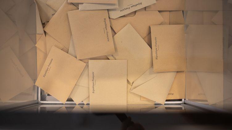 Des enveloppes avec les bulletins de vote dans une urne à Lyon, le 20 juin 2021, pour le premier tour des régionales. (SABINE GREPPO / HANS LUCAS / AFP)
