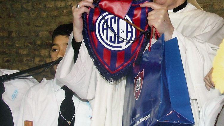 Jorge Mario Bergoglio brandit l'emblème du club de foot San Lorenzo, dont il est supporter,le 13 mars 2013, à Buenos Aires (Argentine). ( AFP )