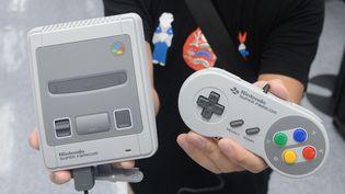 Un homme présente uneSuper NintendoMini àOsaka (Japon), le 5 octobre 2017. (TAKAYUKI HAMAI / YOMIURI / AFP)