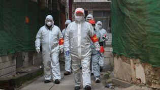 Des personnes visitent un quartier de Wuhan, cœur de l'épidémie de coronavirus 2019-nCoV en Chine, le 9 février 2020, pour s'assurer que tous les malades sont pris en charge. (CHENG MIN / XINHUA / AFP)