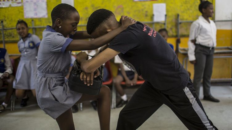 Bouclier de cuir en main, l'instructrice donne ses consignes. Ses élèves du jour, des écolières de 11 ans, s'exécutent sans broncher et rouent la cible de violents coups de genou. Face aux élèves de l'école Thabisang, une des formatrices de l'ONG ABS, Dimakatso Monokoli, donne ses conseils.«Ne commettez jamais l'erreur de vous retrouver seules dans la même pièce que quelqu'un qui vous rend mal à l'aise. Faites confiance à votre instinct», leur lance-t-elle. Et en cas d'agression, «criez autant que vous pouvez». «On ne va pas vous apprendre à donner des coups de poing, mais à vous battre de façon intelligente, sans force», renchérit un de ses collègues masculins.Suivent des démonstrations de coups portés aux tibias, à la veine jugulaire, aux parties génitales. «Vous pouvez aussi arracher les oreilles, les narines», détaille l'instructeur.Les filles passent à l'action. Dans leur uniforme –robe bleu et soquettes blanches –, elles se déchaînent. Quelques rires, mais l'ambiance reste studieuse. Conquis par l'approche d'ABS, qui a sensibilisé plus de 13.000 enfants dans le pays, le ministère sud-africain de la Santé vient de faire appel à l'ONG pour former 160 instructeurs antiviol. (GULSHAN KHAN / AFP)