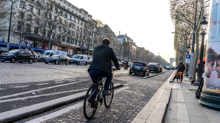 Un homme roule à vélo à Paris. (BRUNO LEVESQUE / MAXPPP)