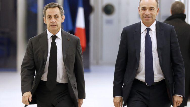 Nicolas Sarkozy et Jean-François Copé quitte le siège de l'UMP, le 3 décembre 2014, après un meeting. (THOMAS SAMSON / AFP)