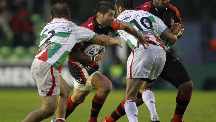 Le Toulonnais Sébastien Tillous-Borde face à deux Biarrots, au Twickenham Stoop de Londres. (IAN KINGTON / AFP)