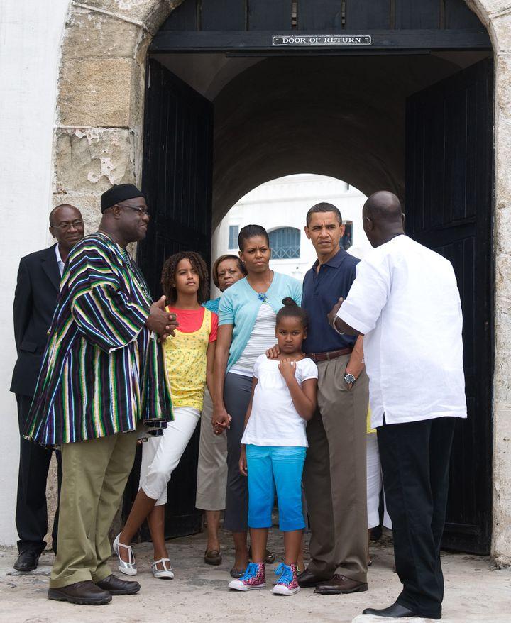 """L'ancien président des Etats-Unis Barack Obama visite en famille le fort de Cape Coast en passant par la """"Porte du non retour"""", le 11 juillet 2009. (SAUL LOEB / AFP)"""