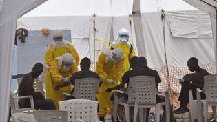 Des médecins en combinaison jaune s'occupent de patients, dans un centre de Monrovia, au Liberia, le 8 septembre 2014. (ABBAS DULLEH / AP / SIPA)
